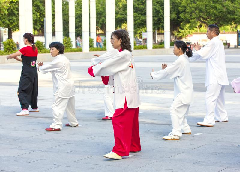 Women and men in the street in the Park gymnastics WUSHU. stock photos