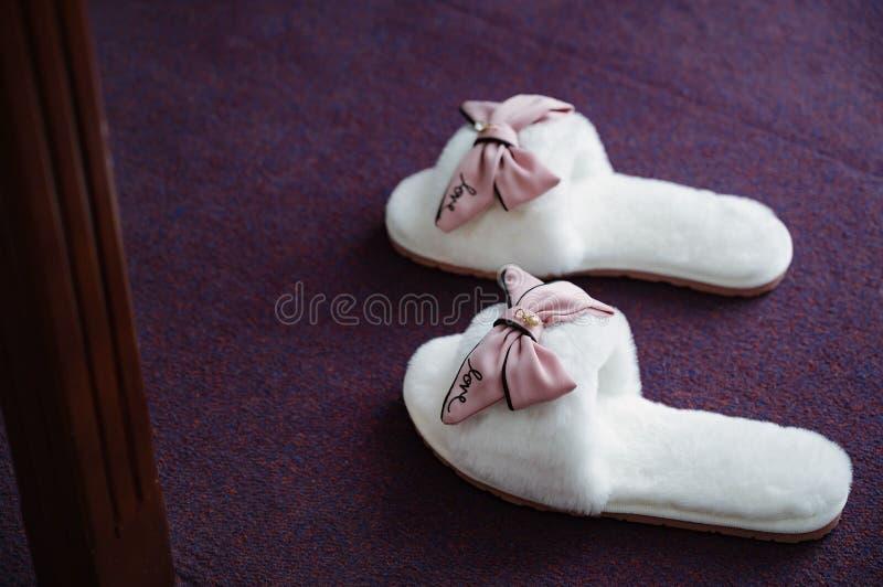 Women& mou blanc x27 ; les pantoufles de s se tiennent dans le plan rapproché de chambre à coucher image stock