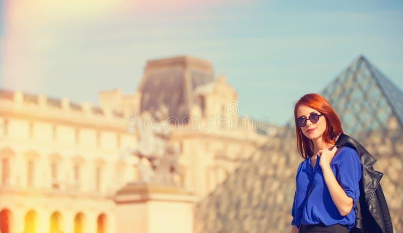 Women near pyramid. Redhead woman near pyramid in Louver, Paris royalty free stock photography