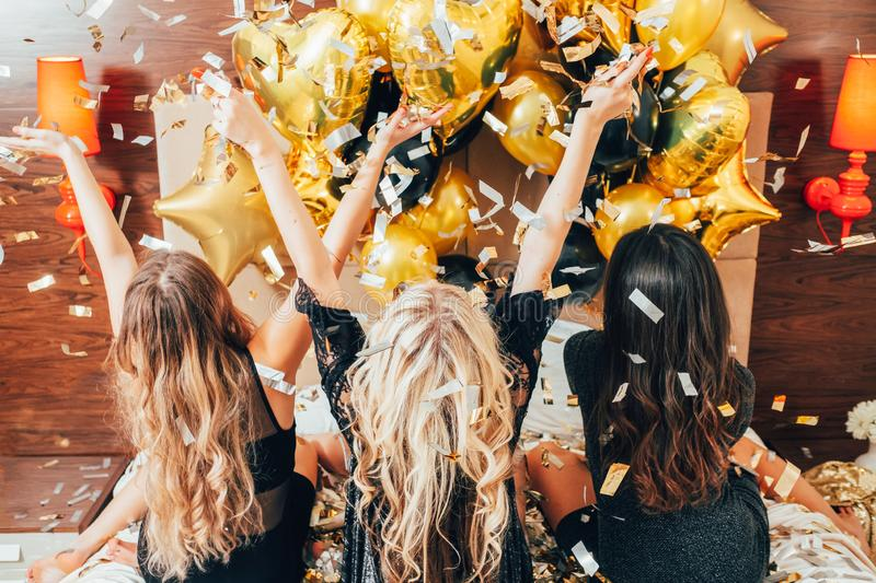Women night party leisure confetti balloons joy. Women night out. Party leisure time. Females on bed catching glitter confetti and balloons. Youth joy and stock image