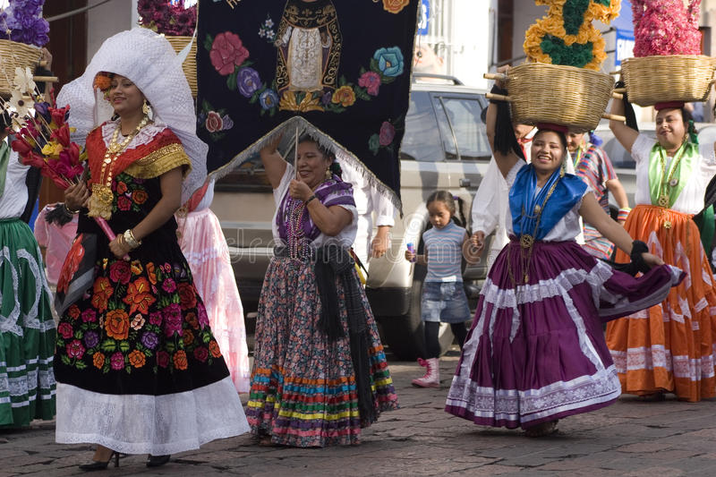 Women from Oaxaca. Women of Oaxaca proud of their traditions carry beautiful dresses in a street parade. Every year during last two weeks of July different