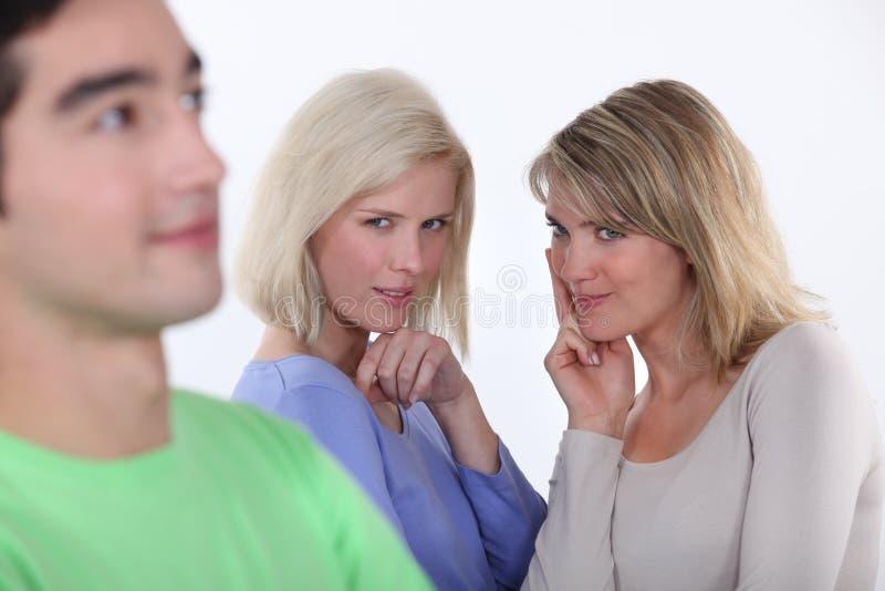 Women observing a man. Young women observing a man stock photos