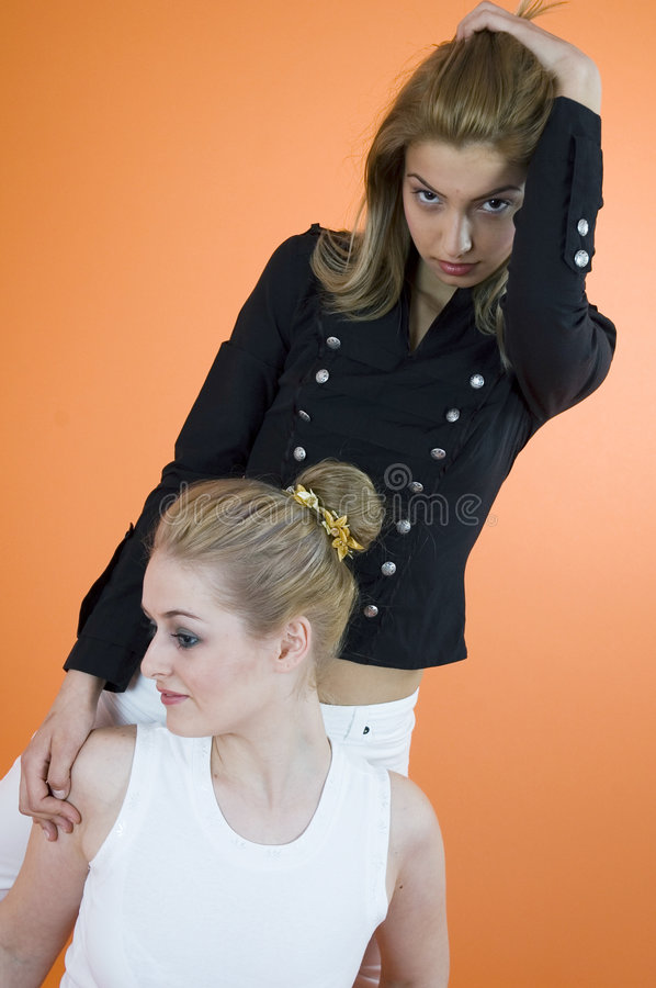 Women Of Opposites. Two young women, one standing behind the other with her hand on one shoulder, with opposing expressions. Taken in studio with an orange stock images