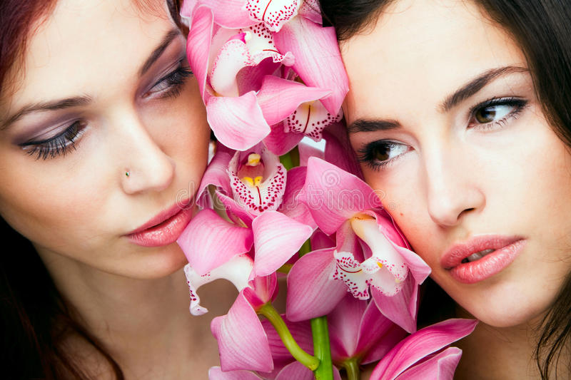 Women with orchid. Red hair and brunette woman beauty portrait with orchid, studio shot stock photography