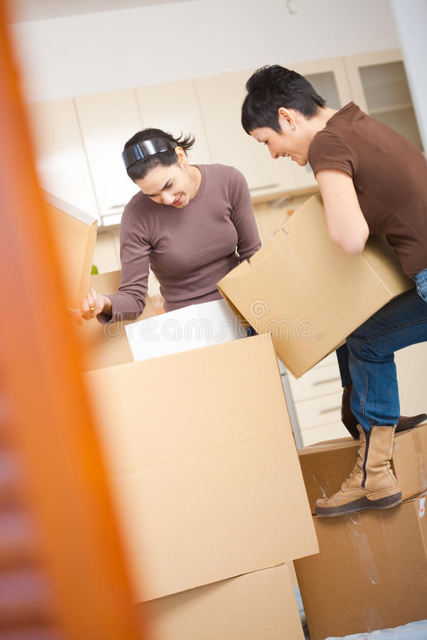 Women packing boxes. Two young women packing up cardboard boxes in kitchen during moving to new home royalty free stock image