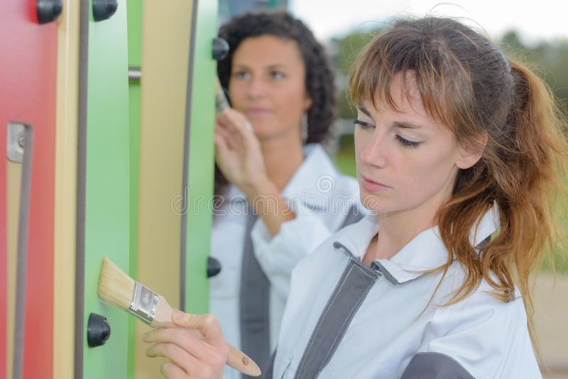 Women painting outdoor play equipment. Park stock photos
