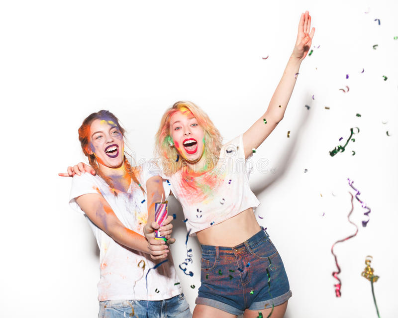 Women with party popper and Holi colors. Two cheerful women covered with Holi colors with the party popper. Horizontal studio shot stock photography