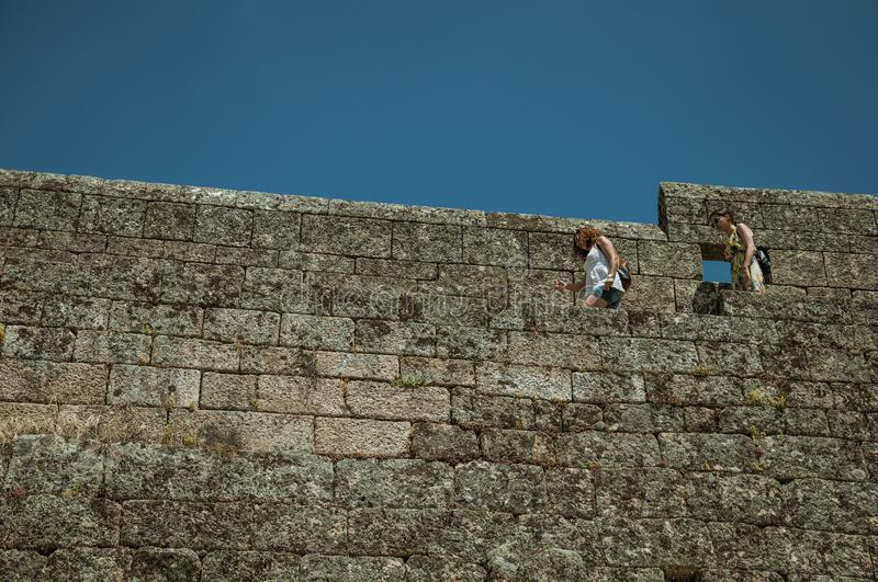 Women passing through a pathway over large stone wall stock photography