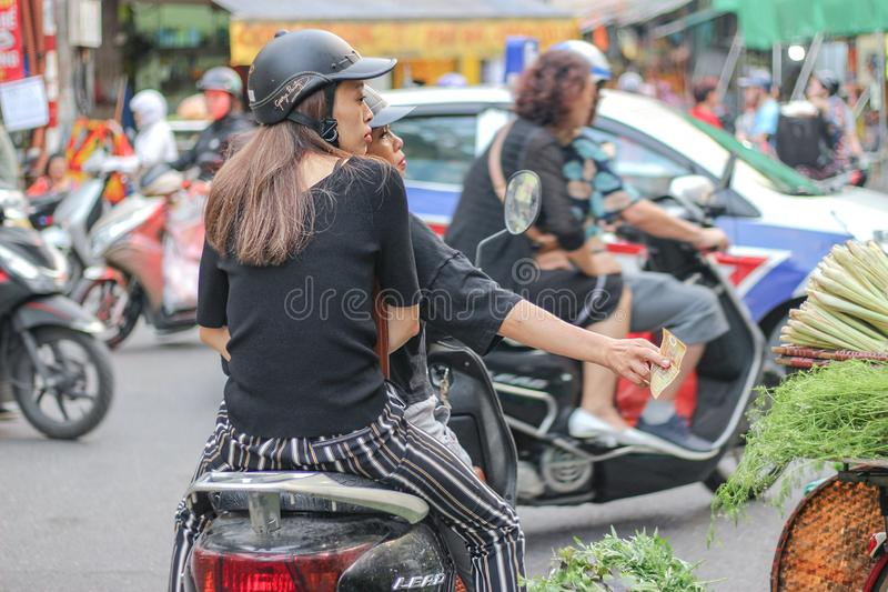 Women are paying by cash on a motorbike in Hanoi, Vietnam. Hanoi, Vietnam - December 02 2018 : Women are paying for vegetables on a motorbike stock photography