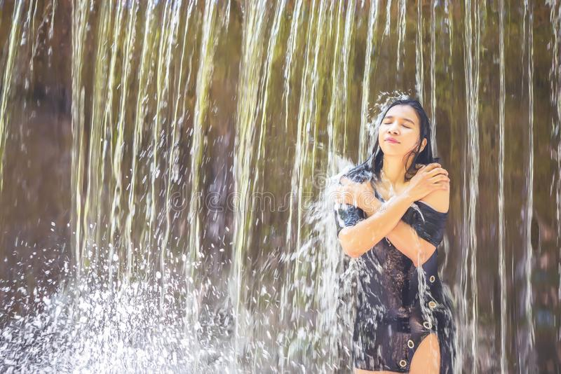 Women peace and playful bathing under waterfall. stock image