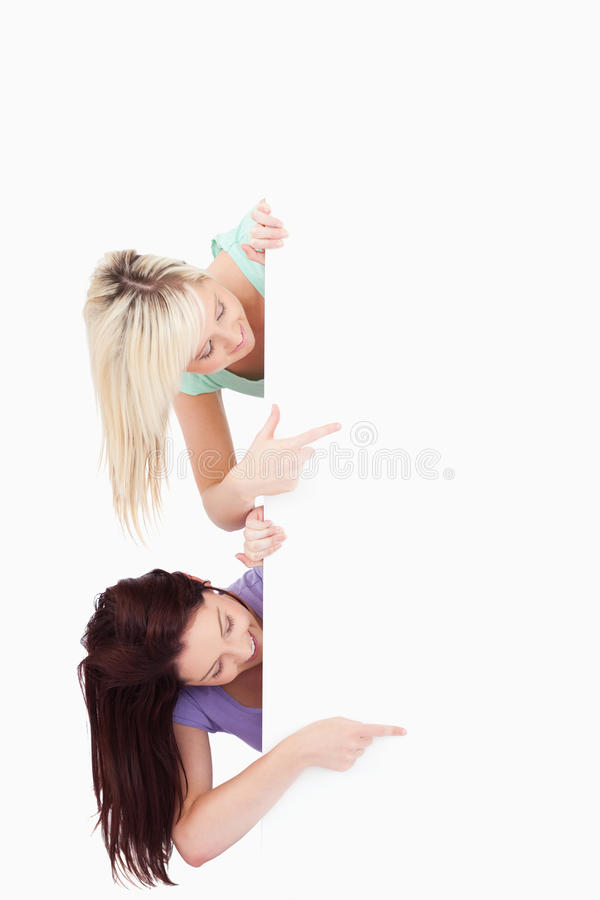 Download Women Peeking Around A Banner Showing Copyspace Stock Photo - Image: 21015778