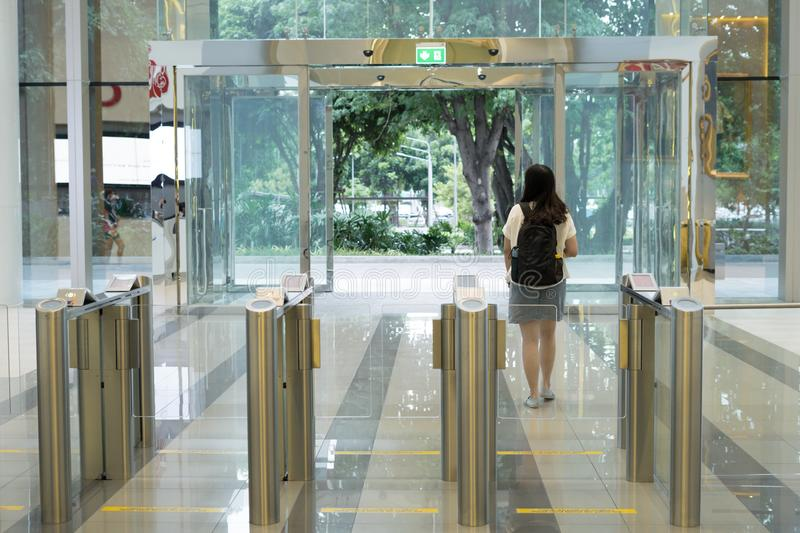Women people walking out from security at an entrance gate with key card access control smart office building stock image
