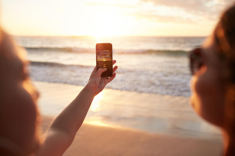 Women photographing sunset with smart phone on the beach. Two young women photographing sunset with smart phone on the beach. Woman hands holding mobile phone royalty free stock image
