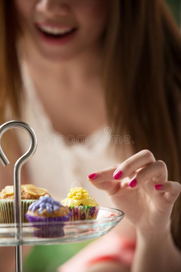 Women are picking cakes from the plate royalty free stock image
