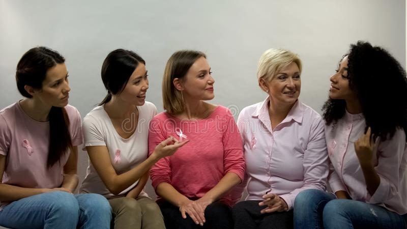 Women with pink ribbons chatting, group of support breast cancer patients health stock image