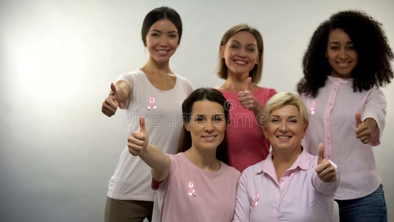 Women in pink shirts with breast cancer ribbon showing thumbs up into camera stock photo