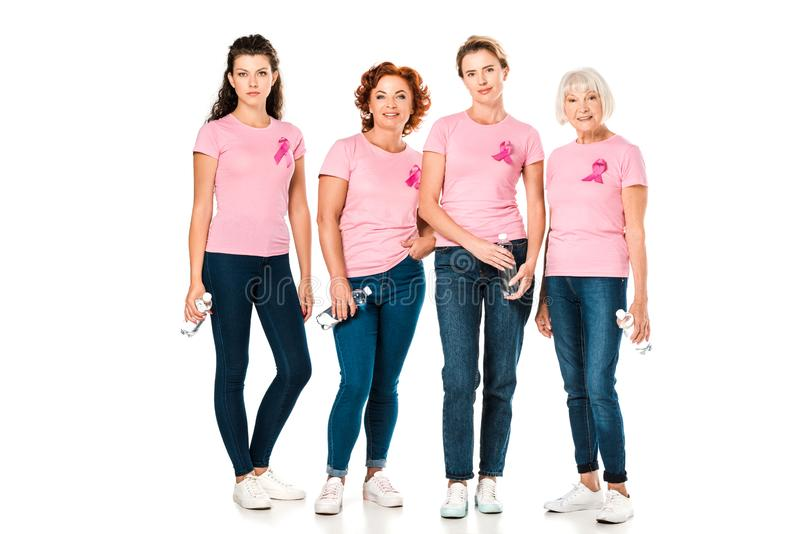 women in pink t-shirts with breast cancer awareness ribbons holding bottles of water and looking at camera stock image