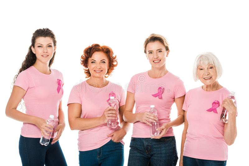 women in pink t-shirts with breast cancer awareness ribbons holding bottles of water and smiling at camera stock image