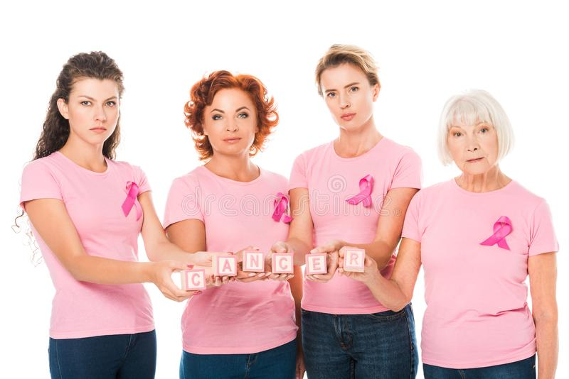 women in pink t-shirts with breast cancer awareness ribbons holding cubes with word cancer and looking at camera stock images