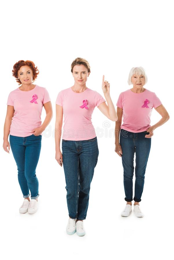 women in pink t-shirts with breast cancer awareness ribbons looking at camera and pointing up with finger royalty free stock photo