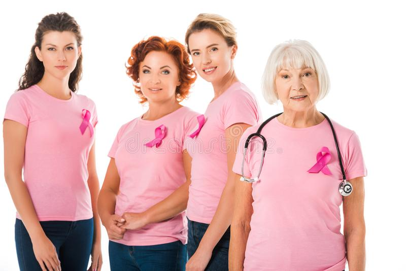 women in pink t-shirts with breast cancer awareness ribbons and senior doctor with stethoscope smiling at camera royalty free stock photography