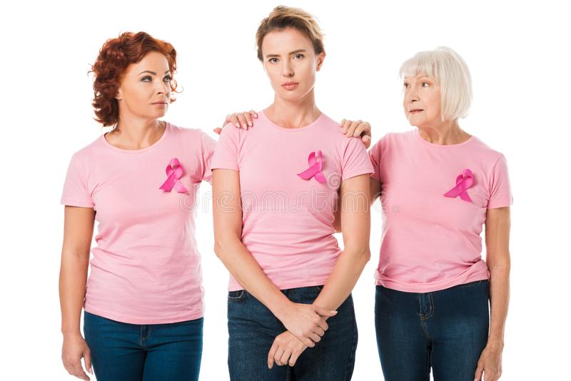 women in pink t-shirts with breast cancer awareness ribbons standing together stock photography