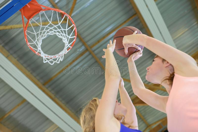 Women plaing basketball aiming for hoop stock images