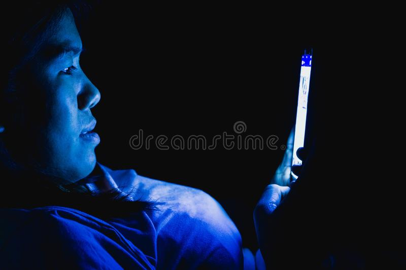 Women she played the smart phone in the dark light and the blue light has a negative effect on the eyes.  royalty free stock photography