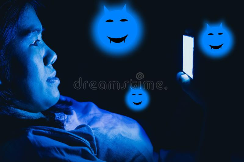 Women she played the smart phone in the dark light and the blue light has a negative effect on the eyes.  royalty free stock photos