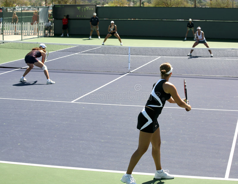 Women playing doubles. Four women playing doubles at the professional tournament stock photo