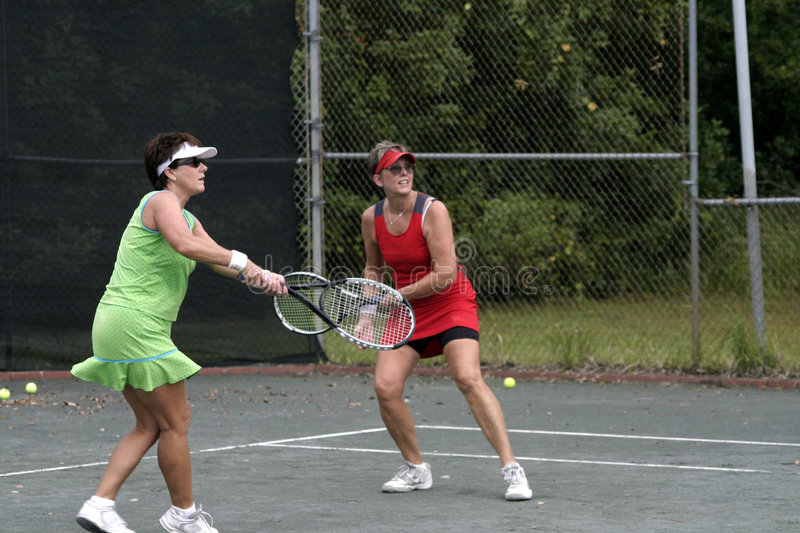 Women playing doubles. Two middle aged Caucasian women playing doubles royalty free stock image