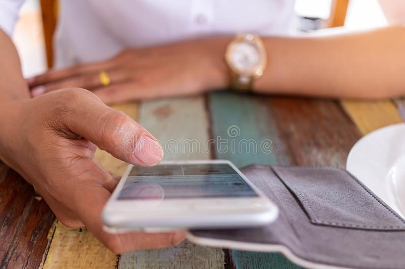 Women playing electronic games on the phone. While waiting food orders in restaurant royalty free stock photo