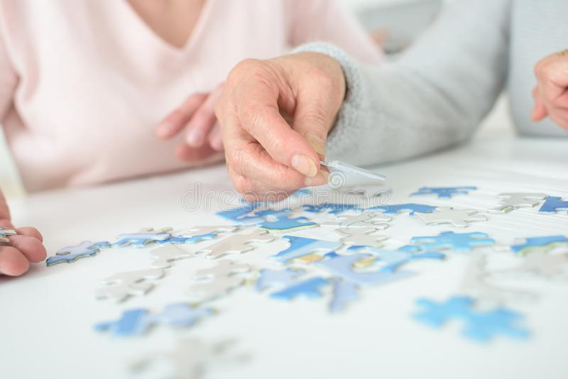 Women playing with jigsaw puzzle on wooden table royalty free stock photography