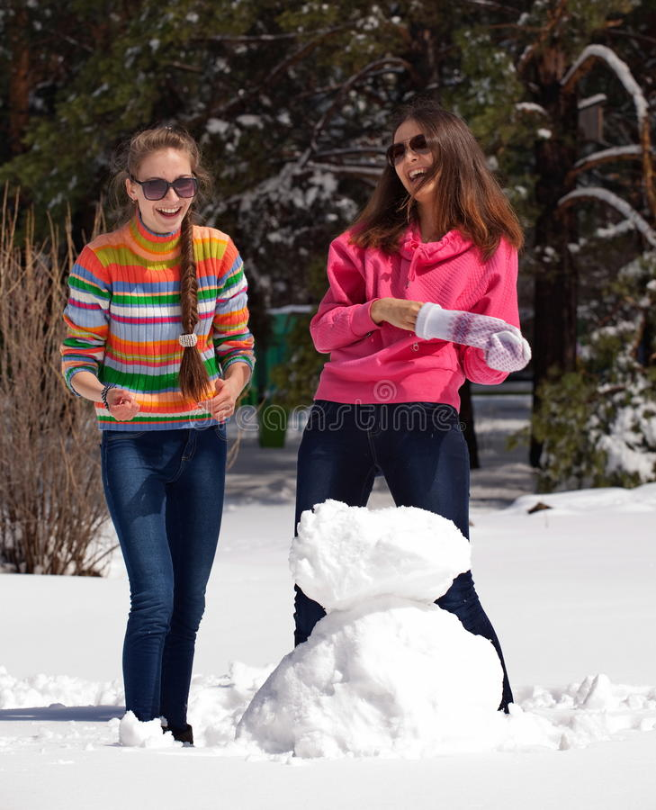 Women Playing With Snowman Stock Image
