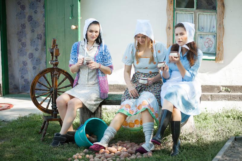 Women on the porch drink tea and talk. Rustic retro style royalty free stock images