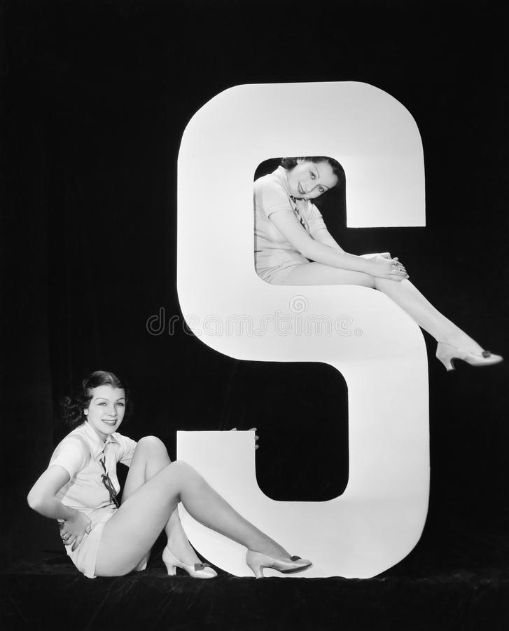 Women posing with huge letter S stock photo