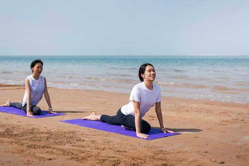 Women practicing yoga on the beach. Asian women practicing yoga on the beach two friends together girlfriends seaside summer mat stretching fitness women workout stock photos