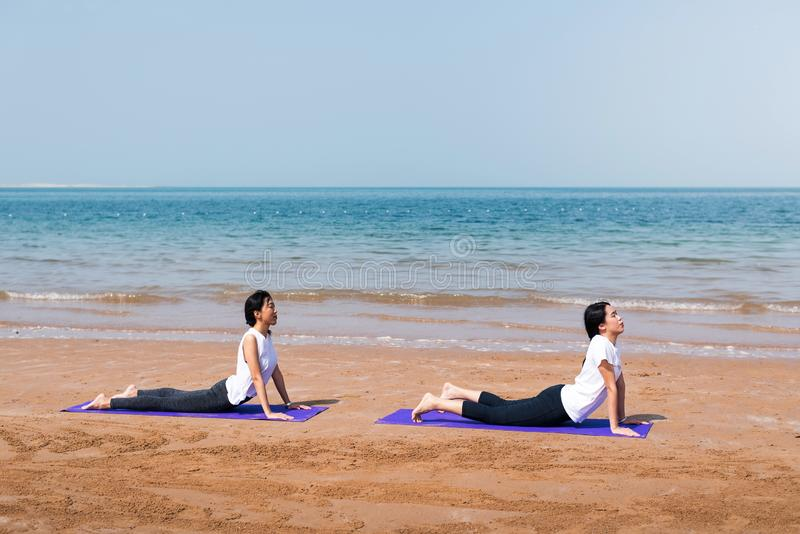 Women practicing yoga on the beach. Asian women practicing yoga on the beach two friends together girlfriends seaside summer mat stretching fitness women workout stock photo