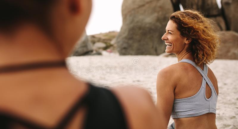 Cheerful women in fitness wear sitting on the beach. Women practicing yoga sitting on beach. Rear view of happy women in fitness clothes relaxing at the beach stock image