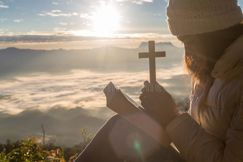 Women pray to god with the cross on the mountain background with morning sunrise. Woman Pray for god blessing to wishing have a. Better life. Christian life royalty free stock photo