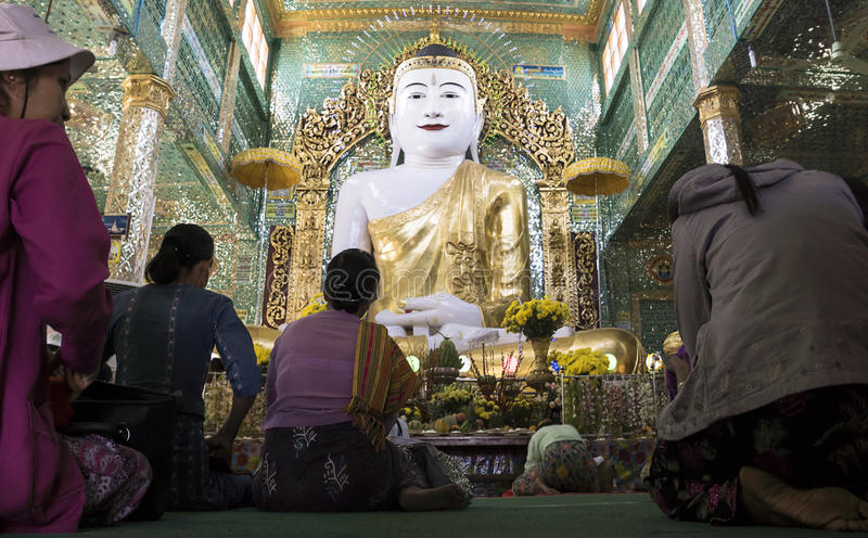 Women praying in temple, Myanmar. Women praying and bowing in front of large Buddha statue in temple in Sagaging, Myanmar royalty free stock photography