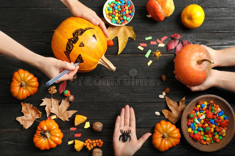 Women preparing Halloween pumpkin head jack lantern and holiday decorations on wooden table, flat lay composition royalty free stock photo