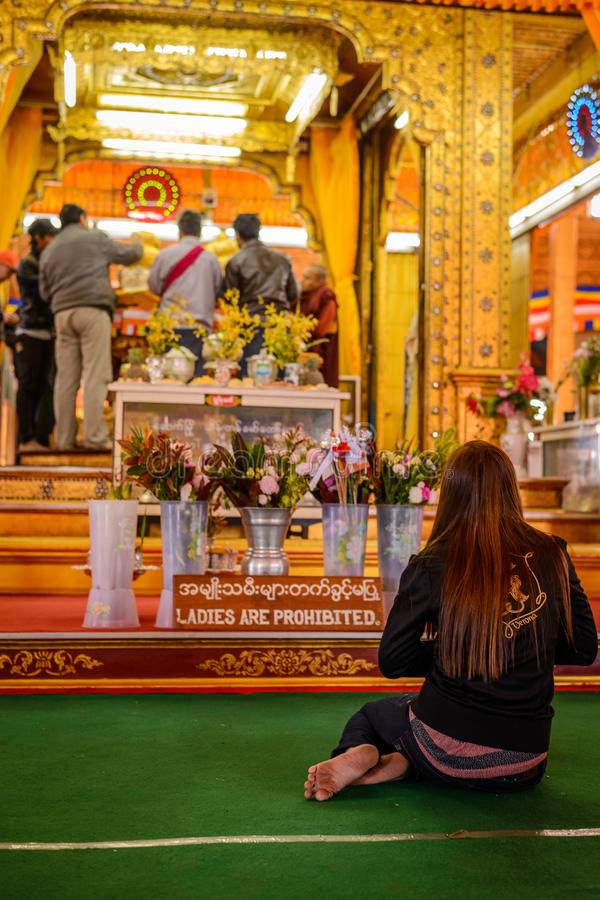 Women prohibited sign with a praying woman in buddhist temple, royalty free stock photos
