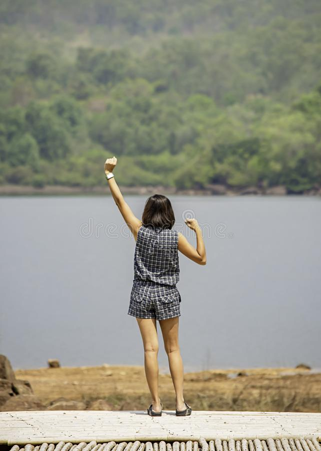 Women raise their arms Background mountains and water at Chakrabongse reservoir , Prachinburi in Thailand.  royalty free stock photography