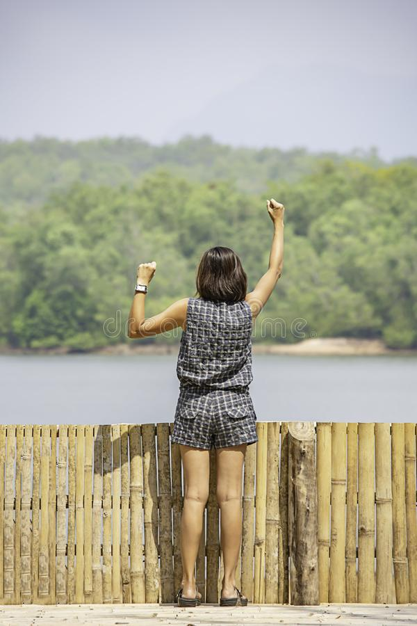 Women raise their arms Background mountains and water at Chakrabongse reservoir , Prachinburi in Thailand.  stock image