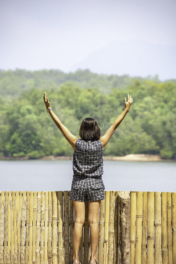 Women raise their arms Background mountains and water at Chakrabongse reservoir , Prachinburi in Thailand.  stock photography