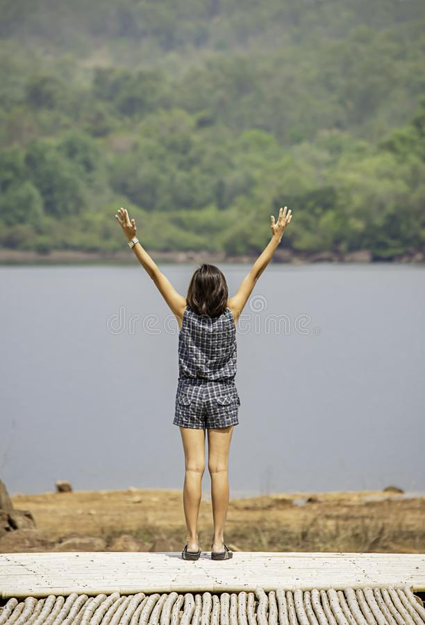 Women raise their arms Background mountains and water at Chakrabongse reservoir , Prachinburi in Thailand.  stock photo