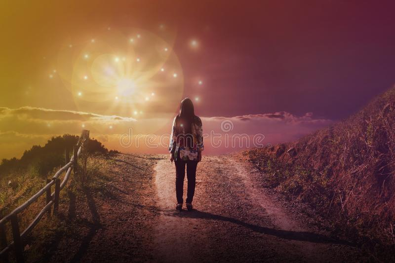 Women rare view standing in front of God sun light flare with dreamy fantasy sky and cloud, women at end of street or way. Women rare view standing in front of royalty free stock photos