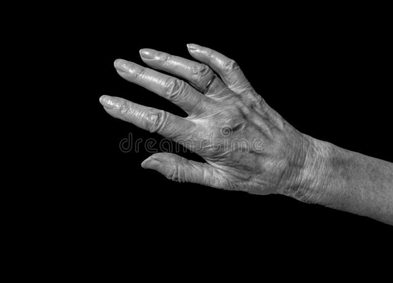 Women reaching hand. A view of old women hand reaching out on a black background royalty free stock image