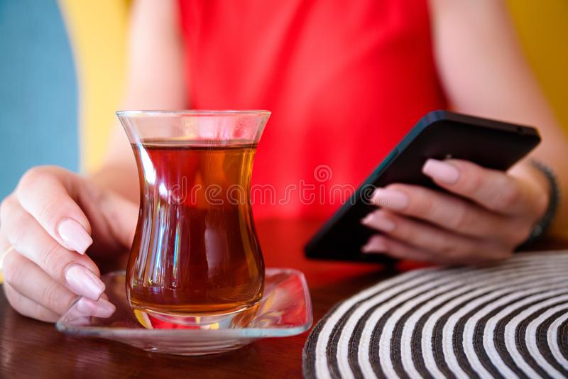 Women in red dress and hand with turkish tea on the wooden table and hat . royalty free stock photography